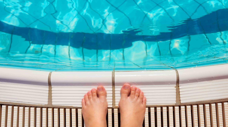 Человек готовится к прыжку в бассейн