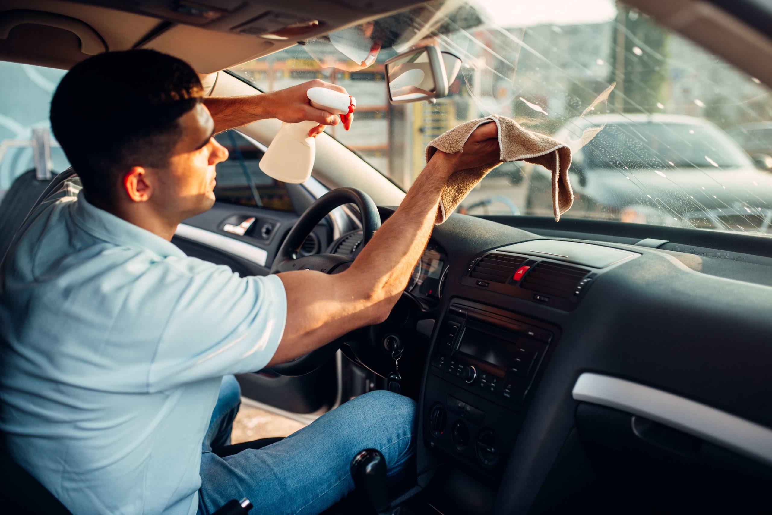Мужчина протирает окно авто
